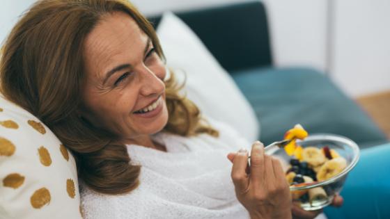 A senior woman smiles as she eats a healthy snack