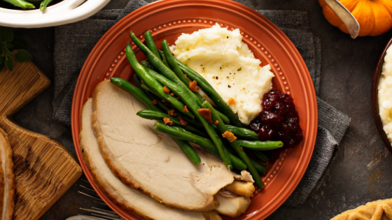 A portioned plate of turkey, green beans, masked potatoes and cranberry sauce