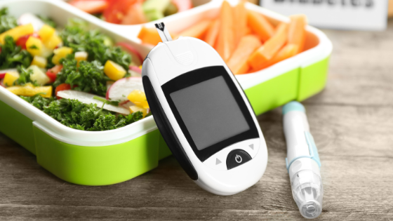 A glucose monitor next to a prepared healthy lunch
