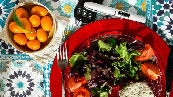 An insulin pen next to a plated salad