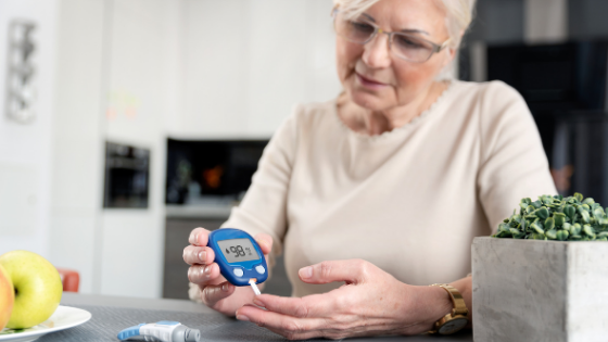 An older woman is seen testing her blood sugar levels in the kitchen