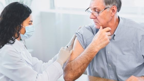 A senior man can be seen getting his yearly flu shot at his doctor's office