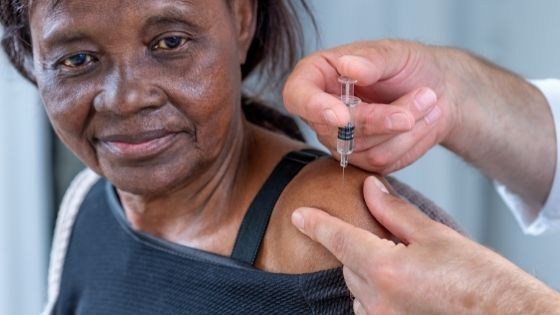 Close up of a senior black woman is seen getting a shot