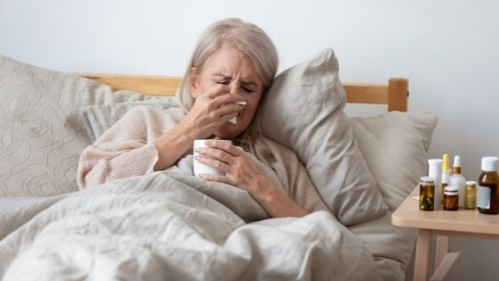 A senior woman is seen sick in bed surrounded by medications