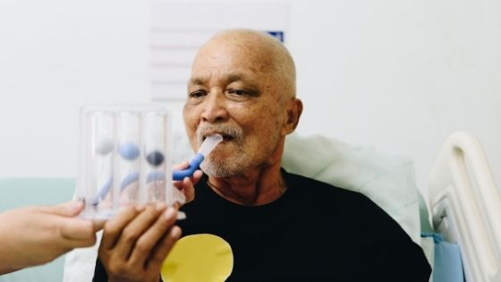 A senior black man is seen blowing into an incentive spirometer