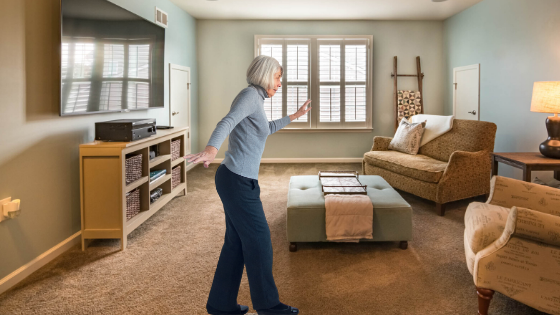 An older woman is seen doing a tandem stance balance exercise in her living room