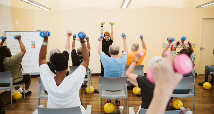 A senior group exercise class where seniors are seen using hand weights