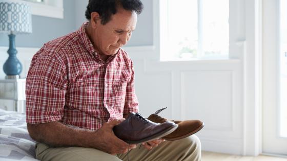 Senior Hispanic man looks confused at his shoes