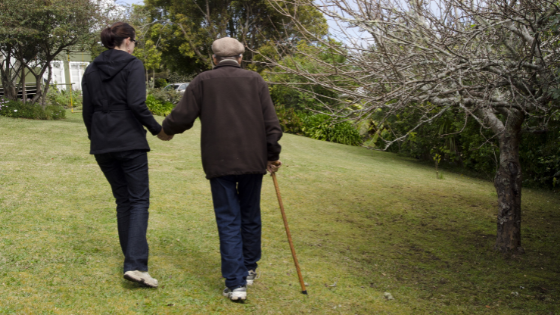 A senior man walks with a younger female using a cane