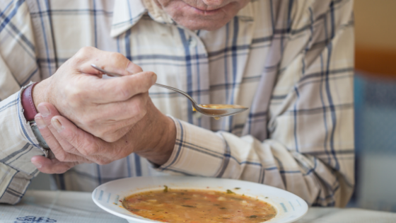 Close up of a senior man with Parkinson's steadying his hand as he eats soup
