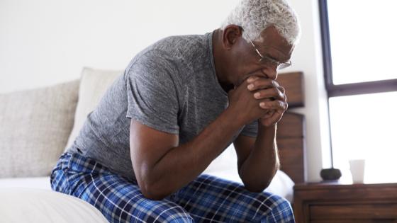 A senior Black man looks concerned sitting in bed