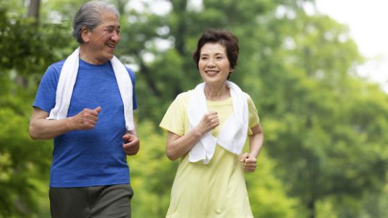 An Asian senior couple power walk in a park