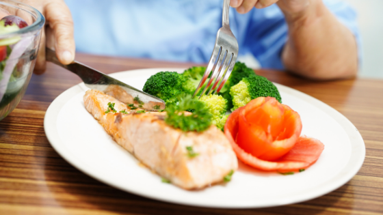 Close up of a senior woman eating salmon and veggies