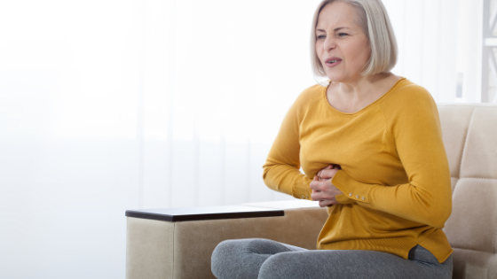 An older woman grips her chest in pain while on the couch