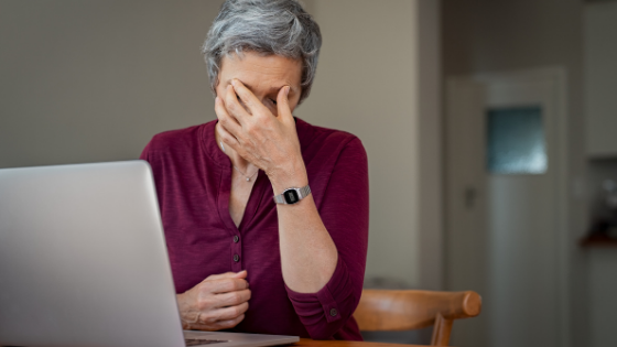 An older woman rubs her eyes while sitting at a computer
