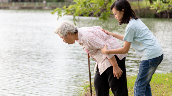A young woman comforts a senior woman as she is nauseated by a lake