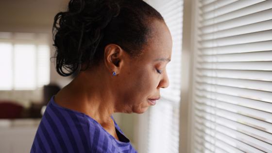 An older senior woman looks sad though blinds