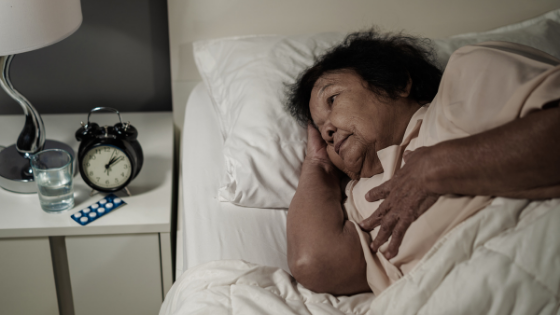 Senior woman lies awake in bed clutching her chest