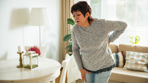 Senior woman hunches over in pain
