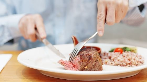 Close up of someone slicing into a steak