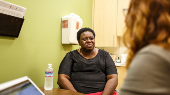 A female patient meets with her doctor in an exam room