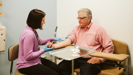 A male patient has blood drawn by a phlebotomist
