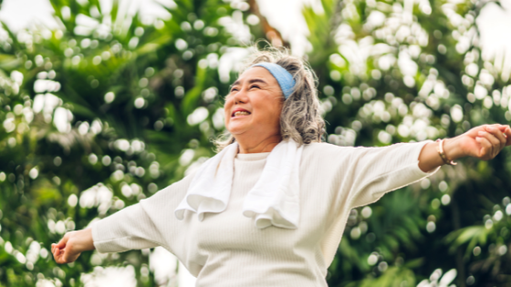 A senior woman smiles as she stretches her arms outward while outdoors