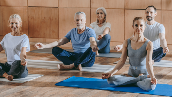 Adults are seated in a yoga class