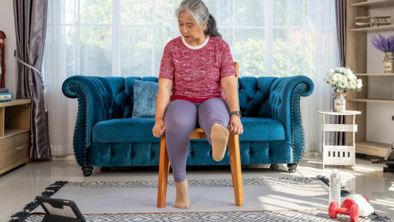 A senior woman watching an exercise video in her living room stretches her foot