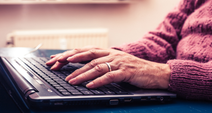 Elderly person seen typing on a laptop