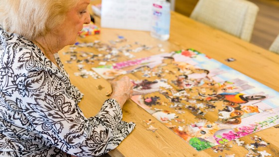 A senior woman is seen doing a puzzle by herself