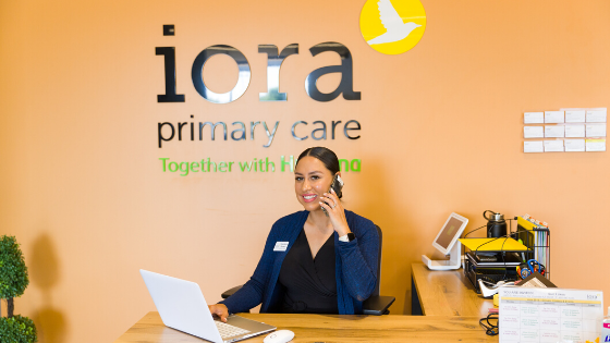An Iora Primary Care OA is seen answering the phone and scheduling appointments