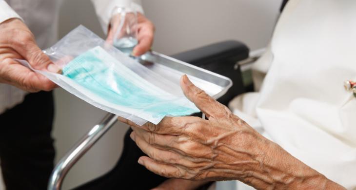 A doctor hands an elderly patient a mask