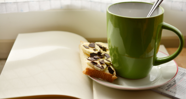 a green mug of coffee sits on a plate with biscuits next to a journal