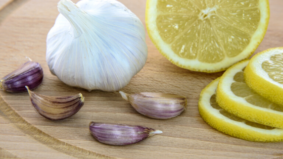 Fresh lemon slices and cloves of garlic on a cutting board