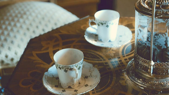 Two cuts of tea sit on a table
