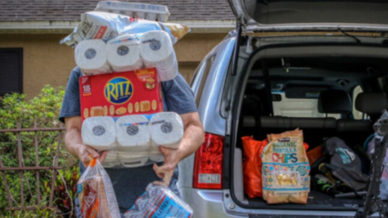 A man is seen loading his SUV with supplies