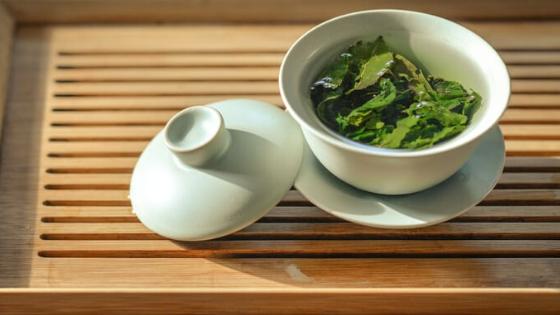 Loose leaf green tea steeps in a white tea cup