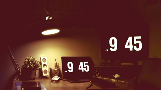 A large clock displays 9:45PM sitting on a desk