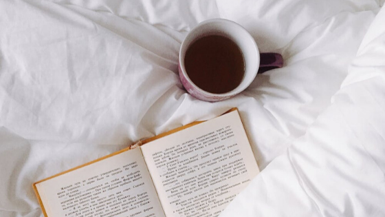 An open book and a cup of coffee in bed