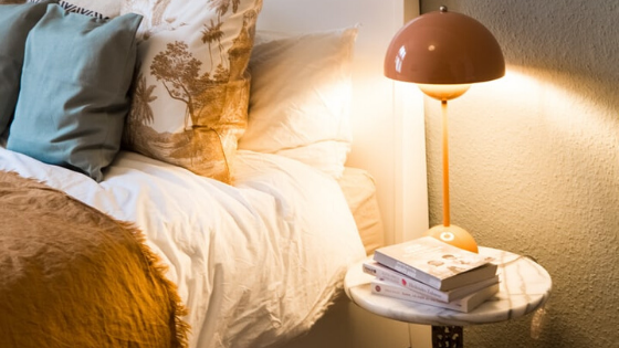 Books on a night stand with lamp next to bed