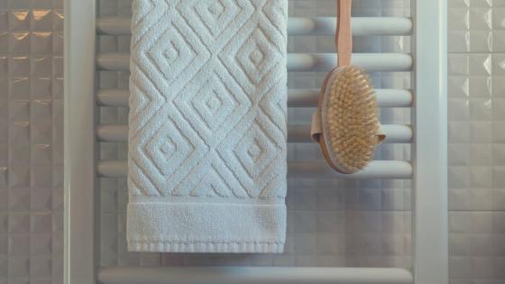 A bath towel and back bath brush hang on a towel rack