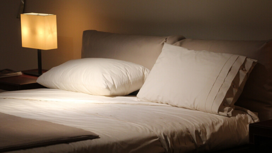 A bed is seen at night time with a lit lamp