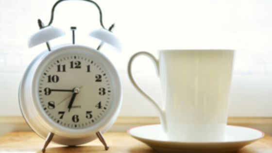 White alarm clock & white mug with saucer