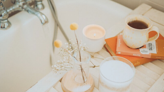 A bath is seen surrounded by flowers, candles, books, and a cup of tea