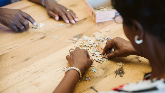 Two people are seen making a puzzle