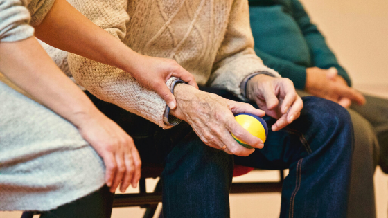 elder adult is seen doing light dexterity exercises with the help of a health coach