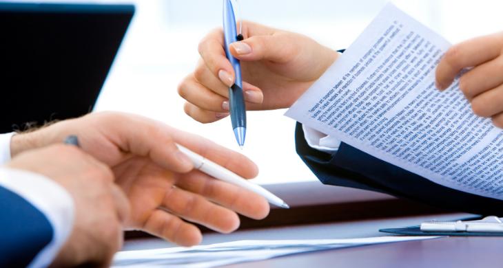 People are seen negotiating paperwork