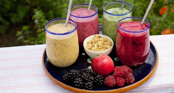Four easy healthy smoothies on a tray with fresh fruit