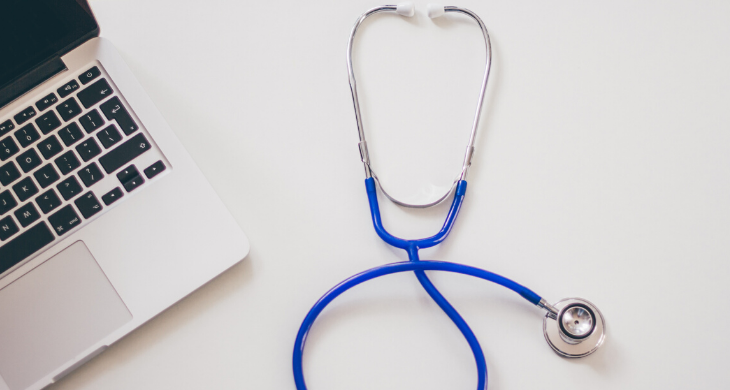 A stethoscope lies next to a laptop